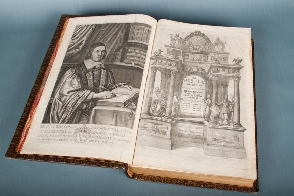 Une photo en couleur montrant un livre ouvert montrant une image d'un homme habillé somptueusement sur la page verso et une frontispice somptueusement illustré sur le recto.