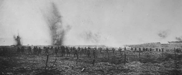 Une photo en noir et blanc de soldats avançant dans un champ pendant que des obus explosent juste en avant de la colonne qui avance.