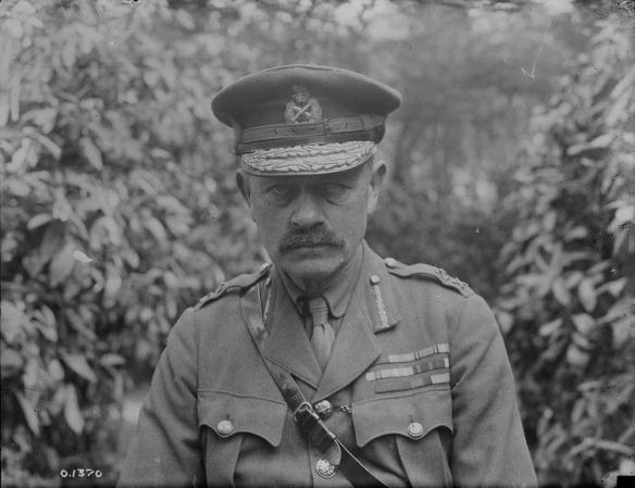 Une photo noir et blanc d'un homme moustachu en uniforme portant une casquette d'officier ainsi que la ceinture Sam Browne. Son blouson est couvert de médailles et de décorations militaires. Il regarde directement le photographe avec un regard impassible.
