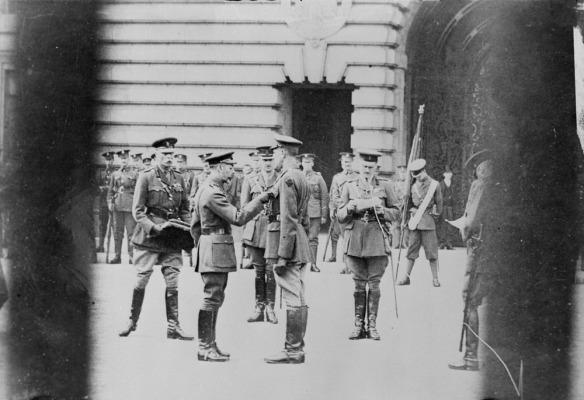 Photographie en noir et blanc d'un homme épinglant une décoration sur la poche de la veste d'un autre homme. Un autre homme lit la citation, alors qu'un quatrième tient une mallette. À l'arrière-plan, des soldats se tiennent au repos.