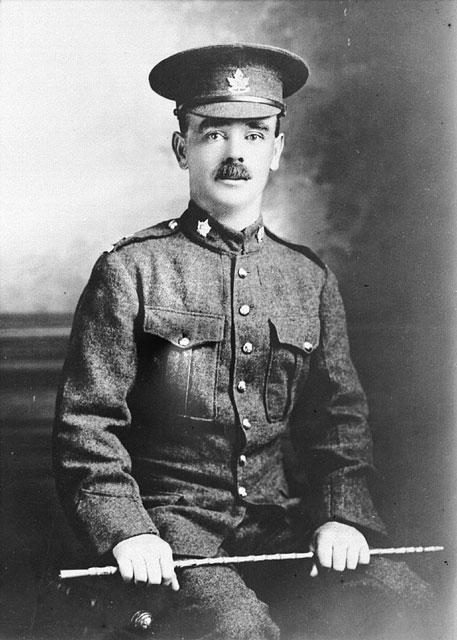 Photographie en noir et blanc d'un soldat assis tenant un bâton et regardant directement le photographe.