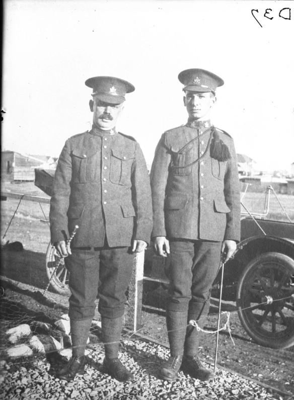 Photographie en noir et blanc montrant deux soldats qui se tiennent l'un à côté de l'autre devant une automobile.