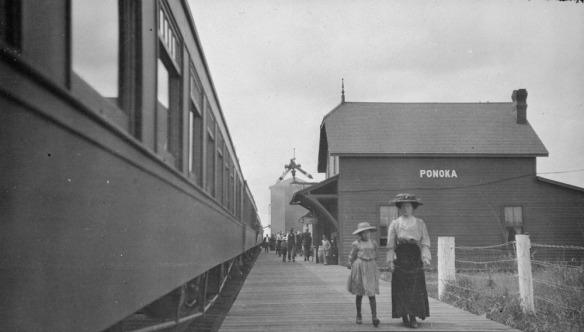 Photographie noir et blanc montrant une femme et une petite fille marchant sur le long d'un quai en bois.