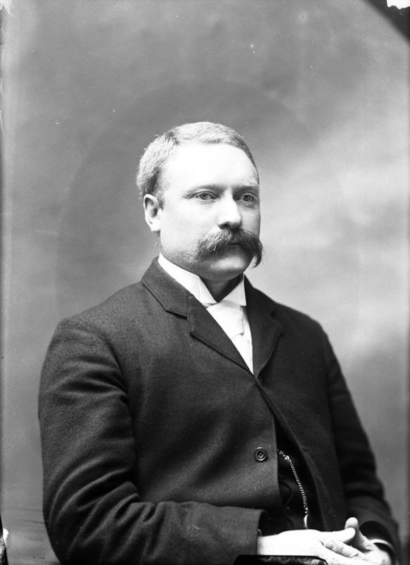 Photo noir et blanc montrant un homme moustachu portant un complet et une chemise blanche.
