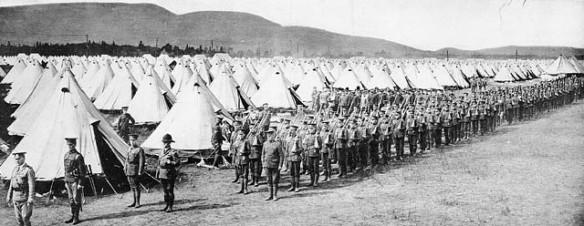 Une photo en noir et blanc montrant un champ de tentes blanches à perte de vue et dans l'avant-plan un long défilé de soldats faisant des exercices militaires.