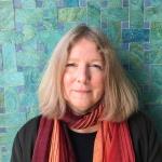 Photographie en couleur d'une femme debout devant un mur turquoise