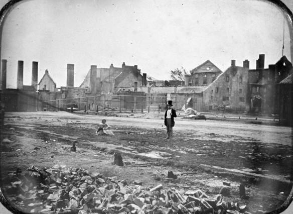 Image noir et blanc des décombres de la brasserie à l'avant-plan, avec un immeuble endommagé en en arrière-plan. Une femme et un bébé sont assis au centre, à la gauche d'un homme debout.