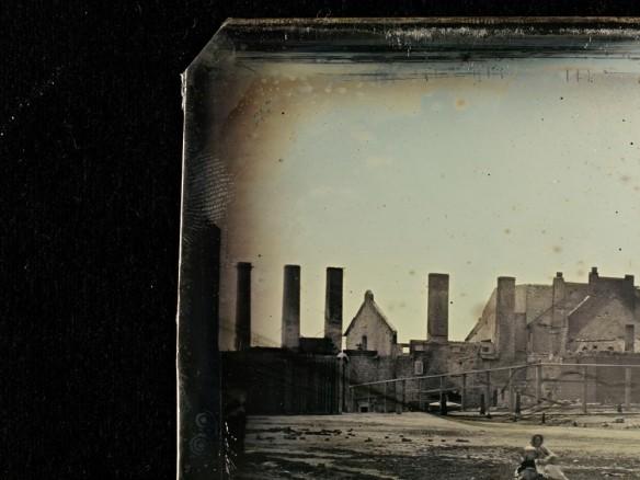 Coin d'un daguerréotype montrant une empreinte digitale sur le bord de la plaque. La photo montre un gros plan de la Brasserie Molson après un incendie. Une femme avec un bébé est assise au bas de l'image.