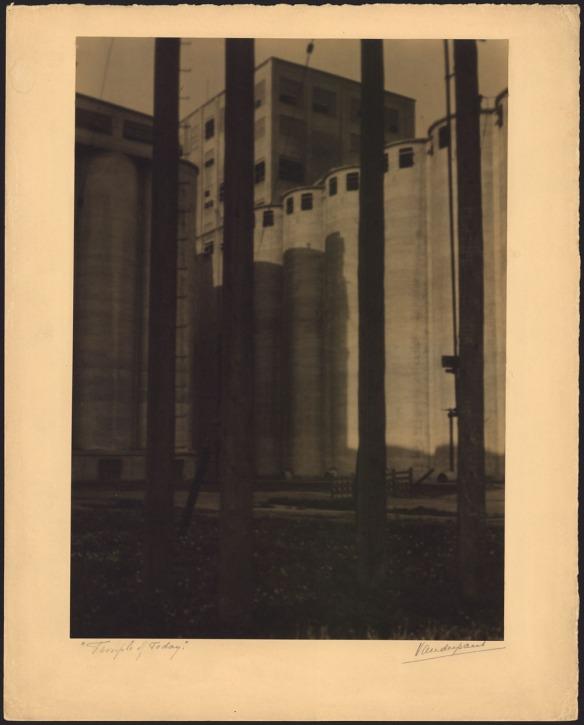 Photographie noir et blanc d'un silo à grains; de hautes tours circulaires se dressent devant un immeuble rectangulaire encore plus haut.
