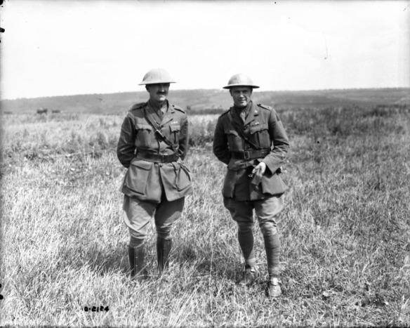 Photographie en noir et blanc de deux hommes en uniforme, debout dans un champ.