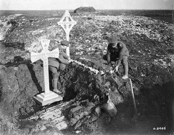 Photographie en noir et blanc de deux hommes qui décorent une tombe de fortune avec des pierres blanches dans un paysage désolant, le sol partiellement recouvert de neige et de gelée. La tombe est surmontée d'une croix arborant les mots « L.S. [Lance-Sergeant] E.W. Sifton, VC » (L/Sgt [sergent suppléant] E.W. Sifton, V.C.) et une feuille d'érable. À côté de la tombe, il y a une autre croix, plus grosse, sur laquelle il est écrit : « RIP Canadian soldiers killed in action 9-4-17 » (Que ces soldats canadiens morts au combat le 9 avril 1917 reposent en paix).