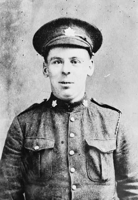 Photographie en noir et blanc d'un homme en uniforme. Sa casquette et son collet sont décorés de feuilles d'érable, et il regarde le photographe.