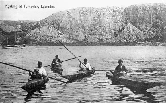 Photographie noir et blanc montrant quatres hommes dans des kayaks avec un grand rocher au lointain.