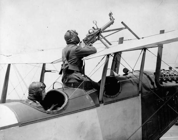 Une photo en noir et blanc montrant un avion biplan avec deux aviateurs dans le cockpit: un qui pilote et l'autre sur la mitrailleuse.