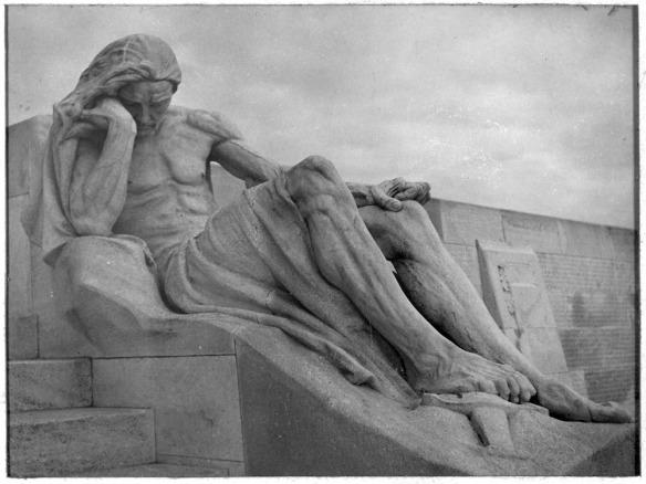 Photographie noir et blanc d'une imposante sculpture du Mémorial de Vimy, représentant un homme endeuillé dont le pied repose sur une épée. En arrière-plan, on voit des panneaux où sont inscrits les noms des Canadiens morts au champ d'honneur.