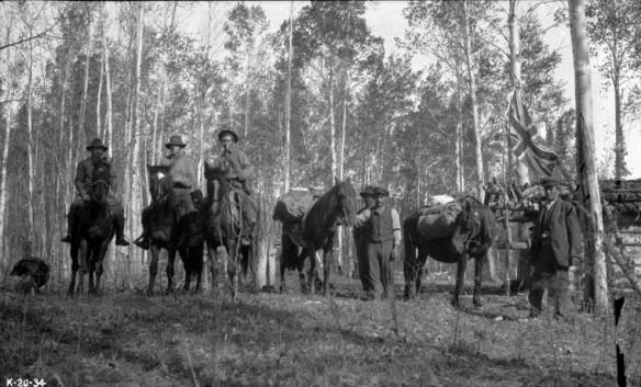 Une photo noir et blanc de six hommes dans une région boisée. Trois sont à cheval et trois autres tiennent leurs cheval par les rennes.