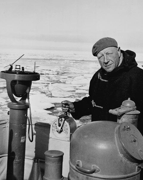 Photographie en noir et blanc d'un homme portant des vêtements d'hiver à bord d'un bateau; on voit l'eau glacée en arrière-plan.