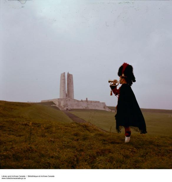 Photographie couleur d'un clairon vêtu d'un uniforme écossais, posant devant le monument sur la crête de Vimy.