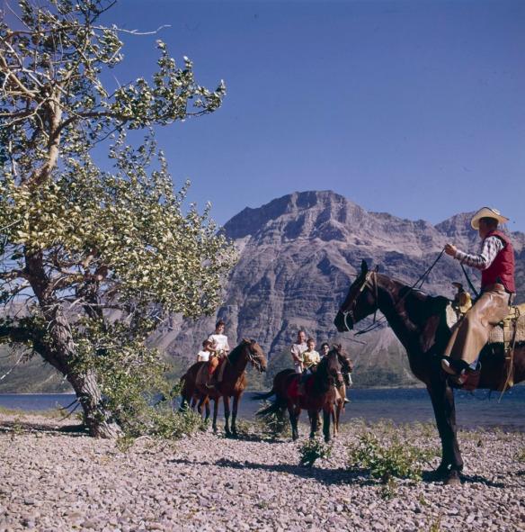 Photographie couleur d'un groupe de personnes à cheval, près d'une rivière. L'un des cavaliers, habillé en cow-boy, semble guider une famille sur un sentier. On voit un pic montagneux en arrière-plan.