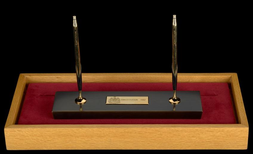 Deux stylos noir et or debout sur un socle noir et or posé sur un bloc en velours et présenté dans un coffret en bois.