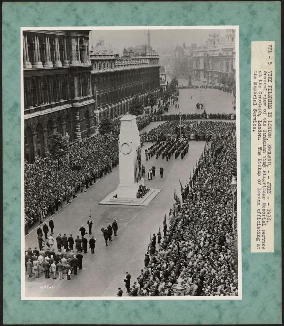 Photographie noir et blanc d'une grande foule sur un trottoir, lors d'une cérémonie. Elle entoure des soldats placés en formation devant un imposant cénotaphe blanc.