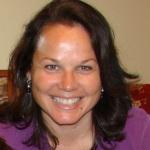 Photo couleur d'une femme arborant un grand sourire.