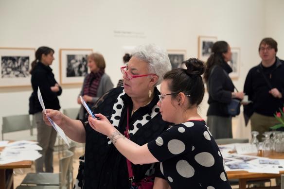 Photographie en couleurs de deux femmes inuites regardant attentivement une photographie. La femme la plus âgée tient la photographie alors que la plus jeune prend une photo de celle-ci avec son téléphone. Derrière elles, des gens parlent et des tables sont couvertes de photos.