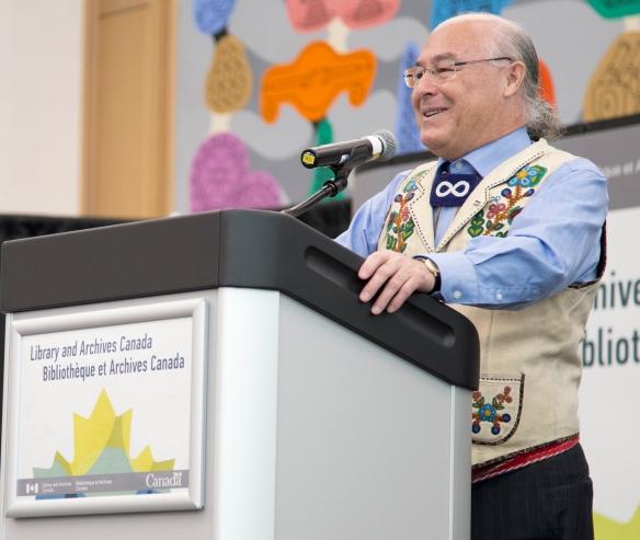 Photographie en couleurs d'un homme de la Nation métisse portant une veste ornée de broderies et se tenant sur un podium.