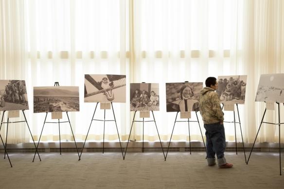Photographie en couleurs d'un jeune Inuit regardant plusieurs grandes photographies sur des chevalets.