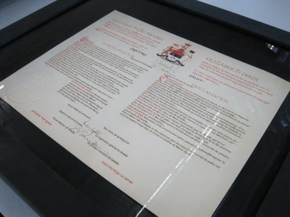 Gros plan du caisson de préservation exposant un exemplaire de la proclamation, sous verre dans un cadre noir.