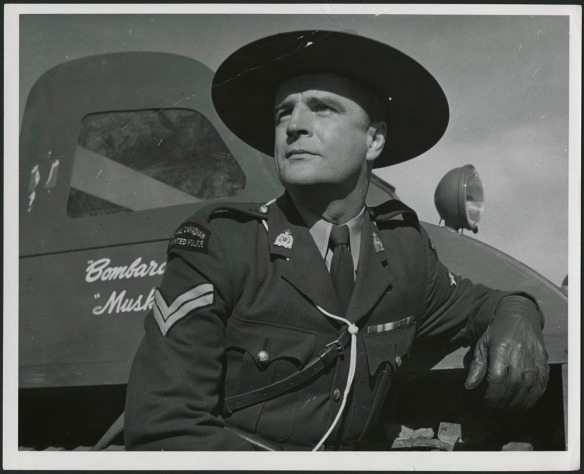Vue fixe en noir et blanc d'un acteur vêtu d'un uniforme de la Gendarmerie royale du Canada (GRC), appuyé contre un camion de marque Bombardier.