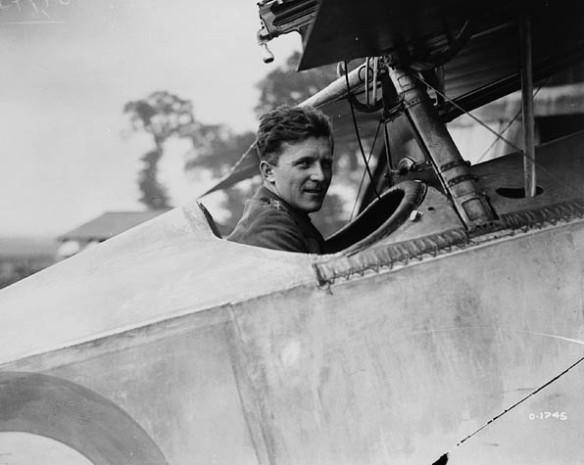 Photographie en noir et blanc d'un homme assis dans le poste de pilotage ouvert d'un avion et regardant le viseur.