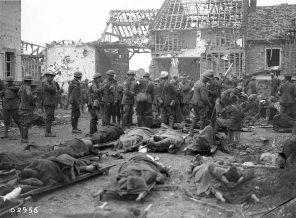 Photo noir et blanc montrant une scène de guerre : des soldats blessés sont étendus sur des civières; autour deux, plusieurs soldats se tiennent debout devant des bâtiments en ruines.