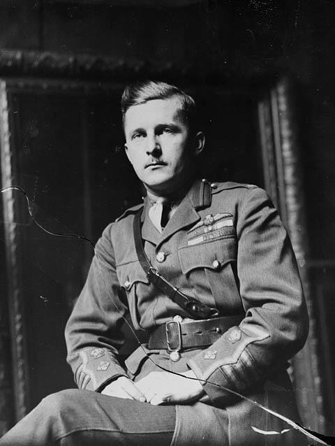 Photographie en noir et blanc d'un militaire assis, les mains sur les cuisses. Il porte la ceinture Sam Browne, une large ceinture en cuir munie d'une courroie plus étroite placée en diagonale et qui passe par-dessus l'épaule droite.