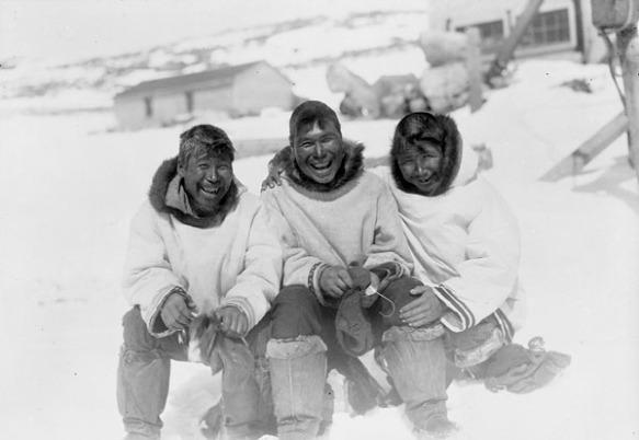 Photo en noir et blanc de trois hommes souriant et assis portant des manteaux traditionnels.