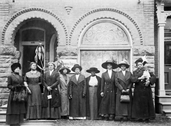 Photo en noir et blanc de neuf femmes portant des robes, manteaux et chapeaux debout devant un immeuble.