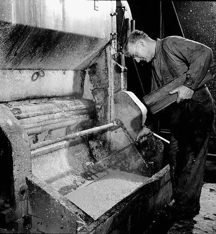 Photo noir et blanc d'un homme tenant une planche de bois, penché au-dessus d'un défibreur.