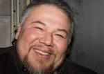 Photo couleur d'une homme avec un grand barbu avec un grand sourire.