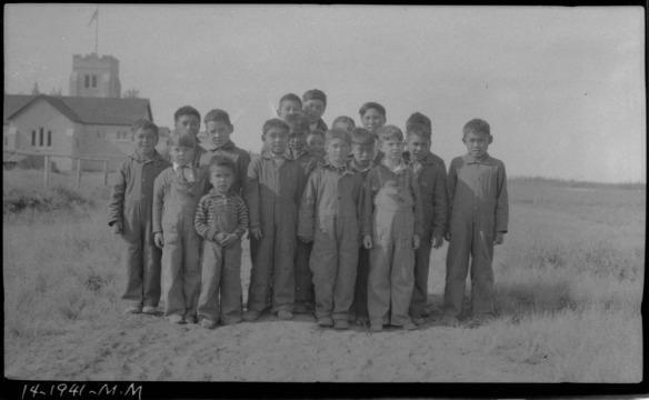 Groupe d'enfants inuits vêtus de combinaisons ou de salopettes, debout sur un sol sablonneux et herbeux, avec l'école en arrière-plan.