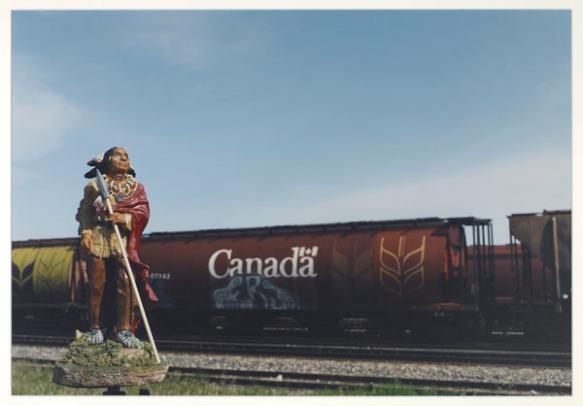 Figurine d'un membre des Premières Nations placée devant un train. On voit l'inscription « Canada » et des graffitis sur le côté d'un wagon à grains.