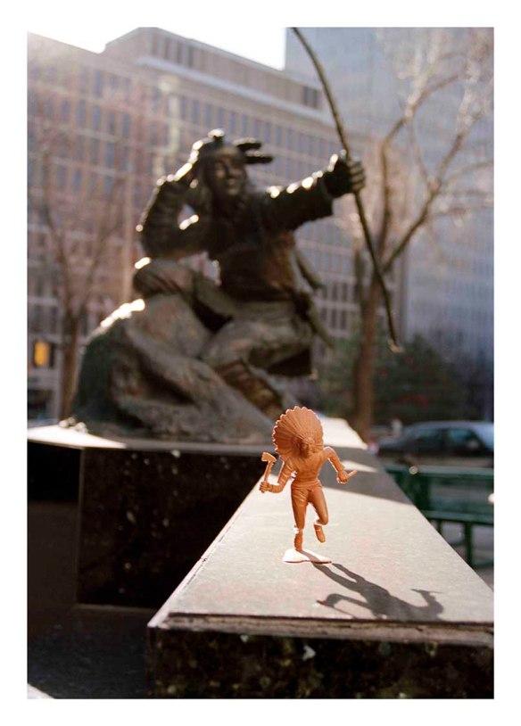 Petite figurine marron clair d'un membre des Premières Nations placée devant la statue d'un chasseur indien. En arrière-plan, on peut voir de grands immeubles à bureaux et des arbres.