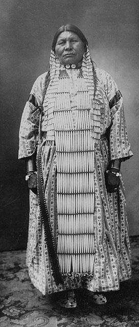 Photo en noir et blanc d'une femme de la Première Nation des Dakota portant une robe rayée sous un long plastron à perles. Elle porte également des tresses, un collier et de longues boucles d'oreilles.