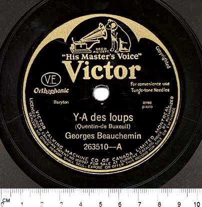 Photographie en couleur d'une étiquette circulaire noire au centre d'un disque 78 tours. En lettres dorées, on peut lire : « His Master's Voice. Victor. Y-A des loups (Quentin-de Bexeuil). Georges Beauchemin. 263510-A ».