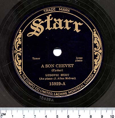Photographie en couleur d'une étiquette circulaire noire au centre d'un disque 78 tours. En lettres dorées, on peut lire « Starr, Tenor, Avec piano, A SON CHEVET (Fyscher), LUDOVIC HUOT (Au piano : J. Allan McIver). 15929-A ».