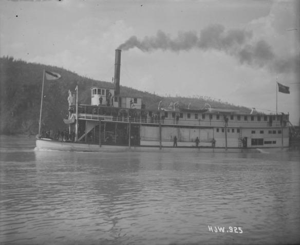 Une photo noir et blanc d'un bateau à vapeur avec des passagers. Des gens sont sur l'avant du bateau tandis que d'autres sont debout sur la passerelle du deuxième étage.