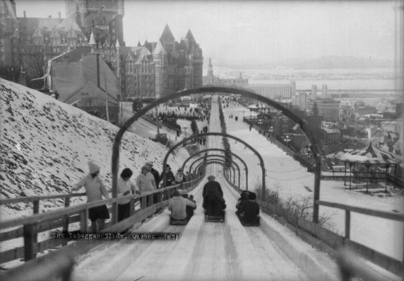 Photographie en noir et blanc de gens sur des toboggans glissant la piste tandis que d'autres personnes montent la cote.