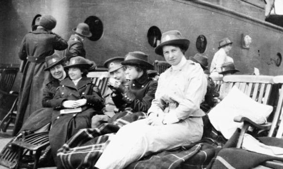 Une photo en noir et blanc d'un groupe de femme assise sur des chaises longue avec des couvertures. Trois des sœurs portent des pardessus foncés tandis qu'une autre en porte un manteau pale. Un soldat peut être entrevue dans le milieu du groupe