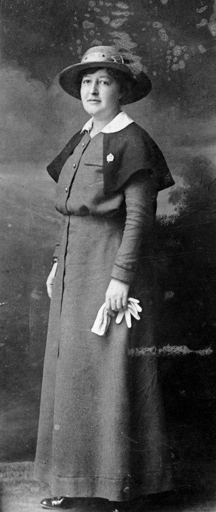 Une photo noir et blanc d'une femme dans l'uniforme d'une sœur infirmière avec la cape, l'épinglette, le chapeau et les gants blanc.