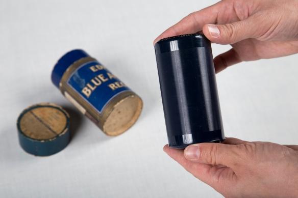 Une photographie couleur de mains tenant un cylindre bleu foncé couvert de sillons. La boîte en carton du cylindre se trouve à l'arrière-plan.