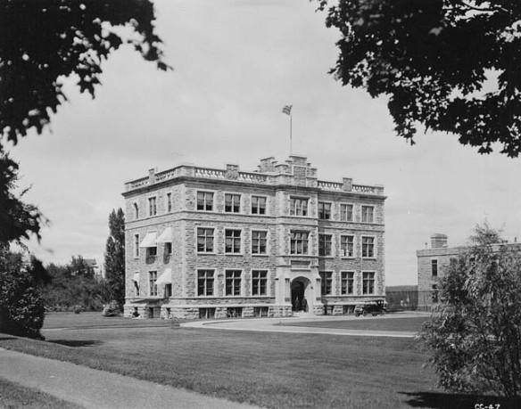 Une photo en noir et blanc d'un edifice de trois étages en pierre situé dans un espace avec une grande pelouse